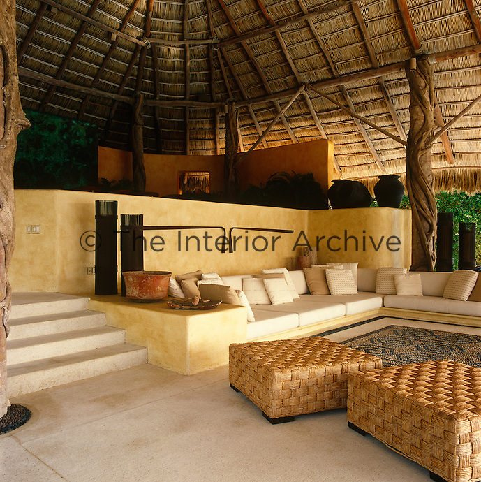 The main living area is built beneath the palapa, or traditional Mexican roof, and features a large built-in sofa and a floor with an inlaid square stone 'rug' made of local stones