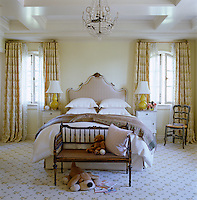 This orderly child's bedroom has a yellow and white colour scheme and patterned carpet and curtains