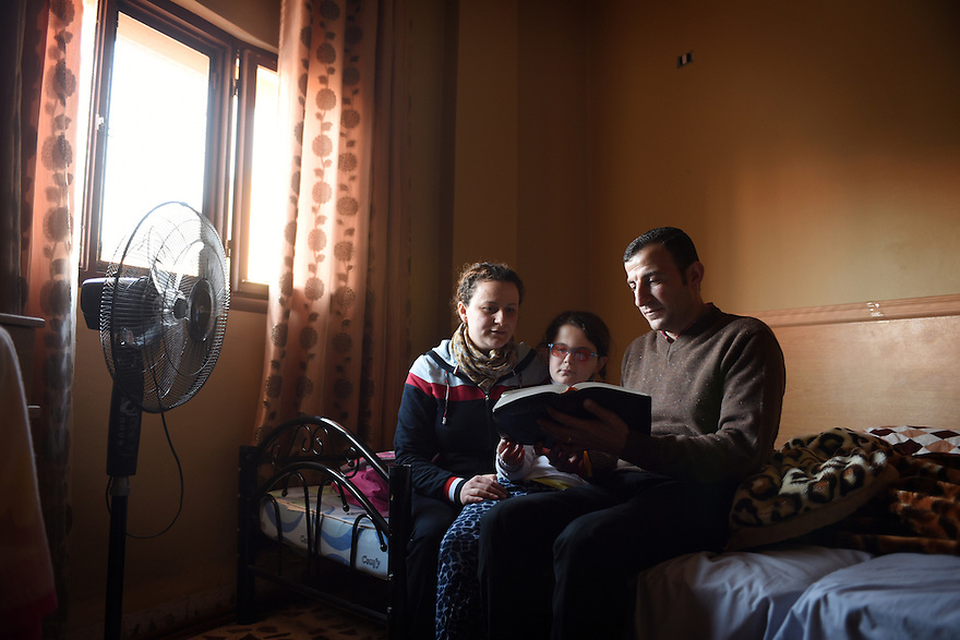 TRAUMA HEALING CASE STUDIES IN JORDAN. RAFED SAKAT, 39, WITH HIS WIFE DIANA, 29 AND THEIR DAUGHTER HEBA, 7, FROM KARAKOUSH, IRAQ, READ FROM THE BIBLE IN HIS NEW HOME IN MADABA, JORDAN. 20/04/16, PHOTO BY CLARE KENDALL.