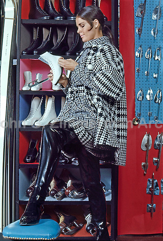 Ali MacGraw models winter fashion and thigh-high vinyl boots at the Princeton Skate and Ski Shop, Princeton, New Jersey, 1967. Photo by John G. Zimmerman