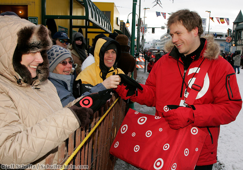 "A Target Store ""ambassador"" hands out one of 10,000 pairs of mittens to spectators along 4th avenue on Saturday March 1st during the ceremonial start day of the 2008 Iidtarod Sled Dog Race. Target is the sponsor for the ""Teacher on the Trail""."