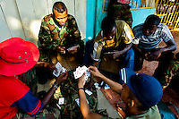 Soldiers of the Colombian paramilitary forces (AUC) playing cards in a jungle settlement Casibare, in the Meta Department, Colombia, 9 April 2006.