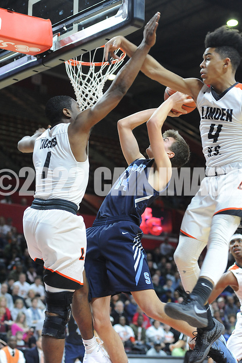 Shawnee's Kane Feudtner (14) attempts a layup as Linden's Khalief Crawford (1) and Luis Rodriguez (4) defends in the second quarter of the New Jersey Group 4 State Championship game Sunday March 12, 2017 at Rutgers University in Piscataway, New Jersey. (Photo by William Thomas Cain)