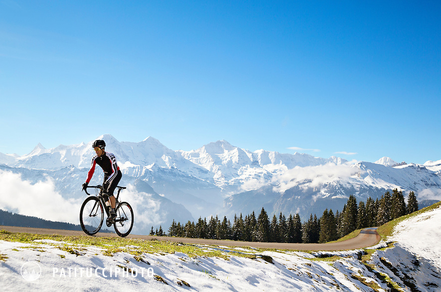 A road biker climbs a small road above Interlaken, Switzerland on a cold, snowy spring morning with views of the Eiger, Mönch and Jungfrau