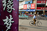 Man riding a bicycle along a busy city street in Datong, Shanxi,China.
