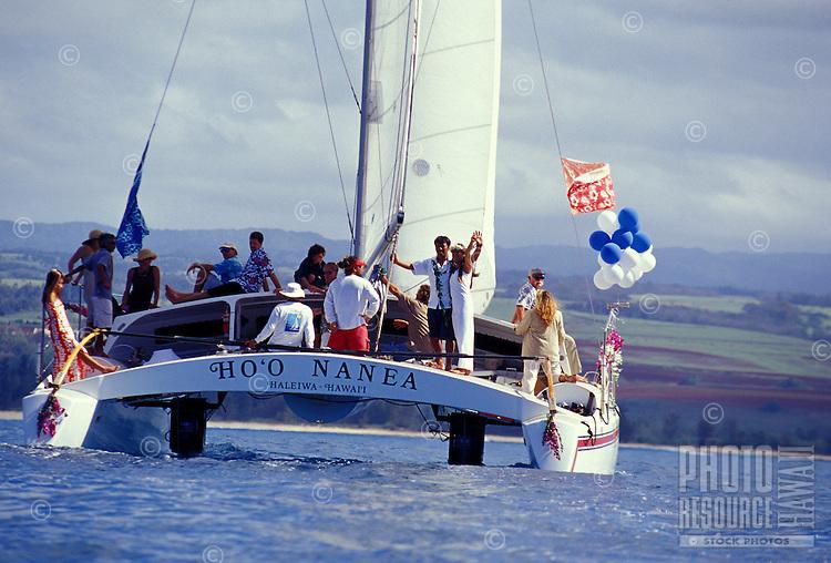 Wedding couple aboard the catamaran Ho'o Nanea, sailing out of Haleiwa Harbor, on the North Shore of Oahu, Hawaii