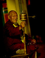 A moment in the day of Buddhist monk at a monastery in the Himalayan foothills of Sikkim, India - an old monk spins his prayer wheel at night.