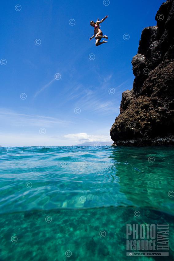 A young woman jumps off Black Rock, Ka'anapali, Maui.