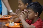 A boy prays before a meal in Knox United Methodist Church in Manila, Philippines. Once a week, the church opens up to poor residents of the neighborhood, offering food, showers, fellowship, a meal, worship, and an educational opportunity for the children.