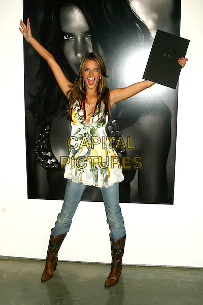 """ALESSANDRA AMBROSIO.Victoria's Secret """"Sexy Volume 3: A Tribute to a Decade of Sexy Swimwear"""" Launch Party,  Milk Studios, New York City, USA, April 5th 2005.full length yellow white floral flower printed top jeans brown boots tucked in black book pointing arms up.Ref: IW.www.capitalpictures.com.sales@capitalpictures.com.©Ian Wilson/Capital Pictures."""