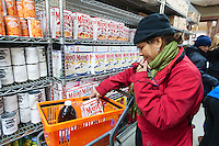 Clients at the West Side Campaign Against Hunger (WSCAH) receive groceries through the supermarket style food pantry on the Upper West Side neighborhood of New York on Friday, December 19, 2014. The clients get to choose their groceries for themselves and their families. In 2014 WSCAH provided food for over 1.1 million meals for nearly 10,000 families. The supermarket-style distribution promotes self-reliance and empowers the clients. (© Richard B. Levine)