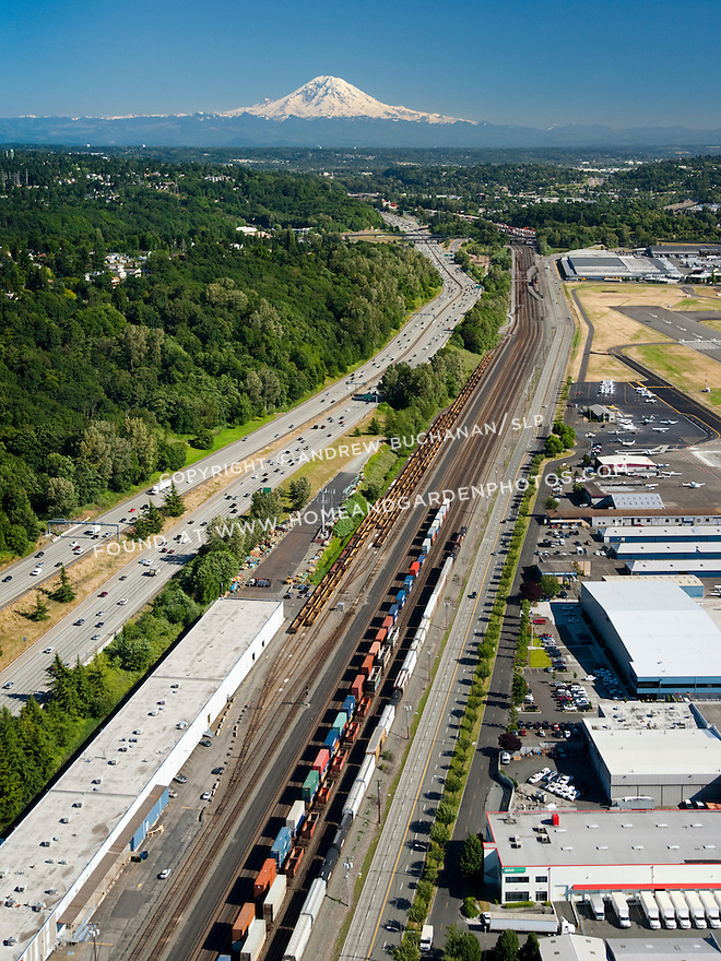 With Mt. Rainier in the background on a sunny day, an aerial view of three modes of transportation: road, rail and air.
