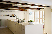 In the kitchen white-painted tongue and groove cupboards complement the restored ceiling beams and light floods in from large louvre-shaded windows