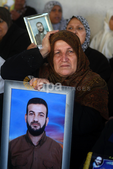 A Palestinian women holds picture of jailed relative during a protest calling for the release of Palestinian prisoners from Israeli jails at the Red Cross office in Gaza City on Jan. 10,2011. Photo by Ashraf Amra