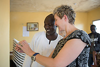 "Occidental College professor Mary Beth Heffernan shows Kabah Trawally his image as she works with ambulance crews at the National Mandingo Caucus of Liberia in Jacob Town, Monrovia, Liberia on Tuesday, March 3, 2015. ""We wish you were here earlier,"" said Trawally.<br /> Professor Heffernan's PPE Portrait Project involves creating wearable portraits of health care workers who must wear PPE, or personal protective equipment. The National Mandingo Caucus of Liberia is an ambulance service that removes dead bodies, in addition to people injured and sick, so crews must wear PPE to help stop the spread of Ebola and other diseases. Ambulance companies, such as this one, must gain the trust of the community in which they are based and hope that placing their images on their PPEs will help.<br /> (Photo by Marc Campos, Occidental College Photographer) Mary Beth Heffernan, professor of art and art history at Occidental College, works in Monrovia the capital of Liberia, Africa in 2015. Professor Heffernan was there to work on her PPE (personal protective equipment) Portrait Project, which helps health care workers and patients fighting the Ebola virus disease in West Africa.<br />