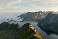 Female hiker on mountain ridge with Reine and Reinefjord in the background, Moskenesøy, Lofoten Islands, Norway