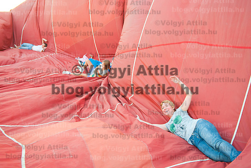 A traveller lies on the balloon to remove hot air from it after landing during the Velence Lake International Hot Air Balloon Festival in Agard, Slovakia on September 10, 2011. ATTILA VOLGYI