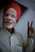Bhartiya Janta Party (BJP) worker shows a victory sign while wearing a face mask of Gujarat's Chief Minister, Narendra Modi at the BJP party office in Ahmedabad, Gujarat, India