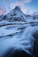 Stortinden mountain peak rises over waterfall in winter, Flakstadøy, Lofoten Islands, Norway