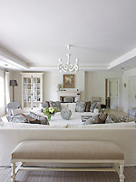 In the living room an antique bench upholstered in beige is situated behind one of the large sofas
