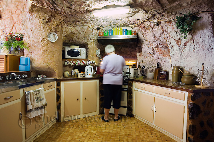 Cooking in the kitchen in Faye's underground home.  The famous home was built by three pioneering women in the 1960s using pick and shovel.  Coober Pedy, South Australia,