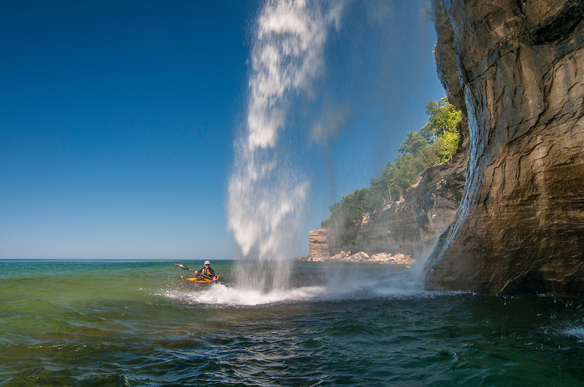 Kayakers paddle near Spray Falls on Lake Superior at Pictured Rocks National Lakeshore near Munising, Michigan.