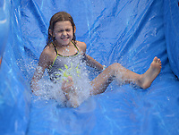 NWA Democrat-Gazette/ANDY SHUPE<br /> Aloysia Reynolds, 8, of Winslow laughs Thursday, July 5, 2018, as she slides down a water slide installed on Block Avenue during First Thursday on the Fayetteville square. The water slide was a new addition to complement the month's theme of &quot;Sweet Summer.&quot;