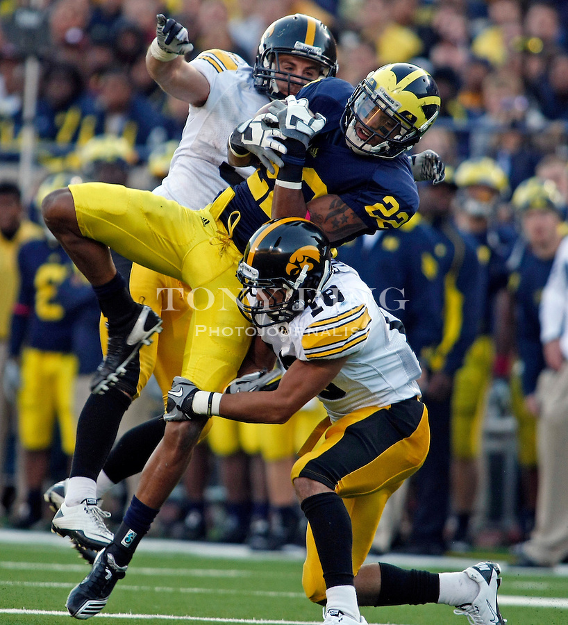 Michigan wide receiver Darryl Stonum (22) catches a 17-yard pass, double teamed by Iowa defensive back Tyler Sash, left, and cornerback Micah Hyde (18), in the fourth quarter of an NCAA college football game, Saturday, Oct. 16, 2010, in Ann Arbor, Mich. Iowa won 38-28. (AP Photo/Tony Ding)