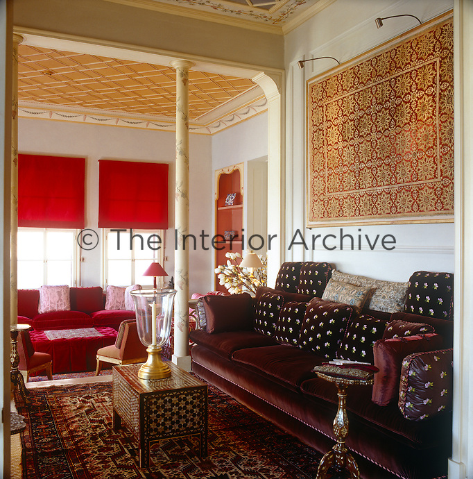 A burgundy velvet sofa dressed with floral patterned cushions is an opulent accompaniment to an intricately patterned rug, wall hanging and inlaid table in this Turkish sitting room