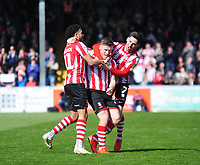 Lincoln City's Shay McCartan, centre, celebrates scoring the opening goal with team-mates Bruno Andrade, left, and Tom Pett<br /> <br /> Photographer Andrew Vaughan/CameraSport<br /> <br /> The EFL Sky Bet League Two - Lincoln City v Cheltenham Town - Saturday 13th April 2019 - Sincil Bank - Lincoln<br /> <br /> World Copyright © 2019 CameraSport. All rights reserved. 43 Linden Ave. Countesthorpe. Leicester. England. LE8 5PG - Tel: +44 (0) 116 277 4147 - admin@camerasport.com - www.camerasport.com