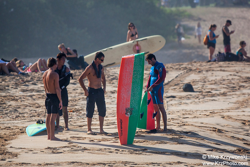 Surfers on the beach holding broken surfboard, Waimea Bay, North Shore, Oahu, Hawaii