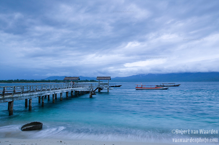 Evening on a pier on the tourist island of Gili Trawangan, Lombok, Indonesia. Moving waves and fishing boats under a cloudy sky fill the frame.