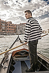 A Venetian gondoleer is taking his gondola across the Grand Canal.