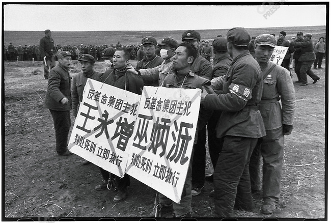 """Before their execution """"counterrevolutionaries"""" Wu Bingyuan (with his eyes closed) and Wang Yongzeng bear placards with their names and crimes. Outskirts of Harbin, 5 April 1968"""