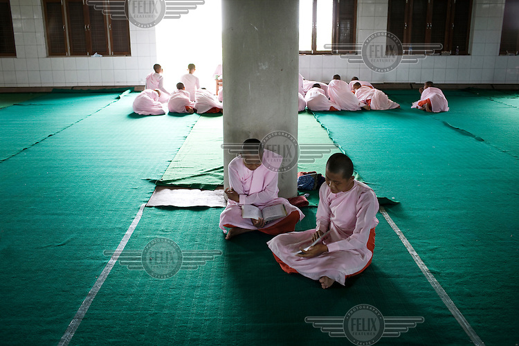 Nuns studying at a monastery in Mandalay. Buddhist nuns are not treated with the same reverence as their male counterparts, having to prepare their own food, and living in monasteries that are often pushed to the outskirts of town. The monasteries themselves are usually less well kept than the monks' monasteries due to a lack of funds....