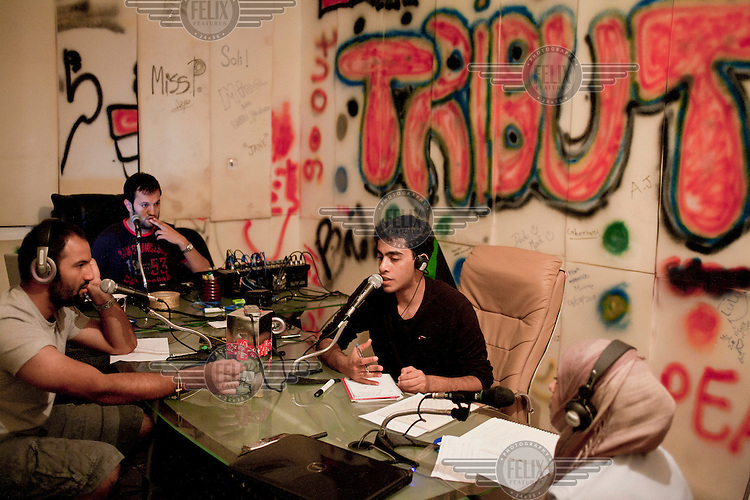 Some of the team behind the new radio station 'Tribute Fm', which broadcasts in English every evening, present a show from their studio in Fuwhaat district of Benghazi.