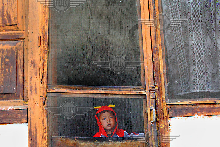 A child peers out of a window from his house.
