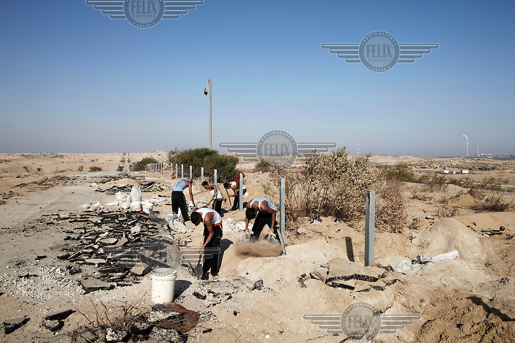 Teenagers searching for gravel dig under an old settlement road running parallel to the Israel border, which is a mere 50 metres away. Many Palestinians have been shot by Israeli army snipers in this area while gathering building materials.
