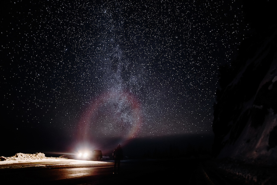 A solitary figure gazes toward the Milky Way as he is partially illuminated by his SUV, creating a circular rainbow flare.