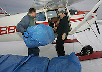 Saturday, Feb. 18, 2006  Anchorage, Alaska. Volunteer Iditarod Airforce chief pilot John Norris and a volunteer load straw into his Cessna plane prior to flying them  out to checkpoints along the trail.  Each musher is given one bale of straw at a checkpoint to bed their dogs down.