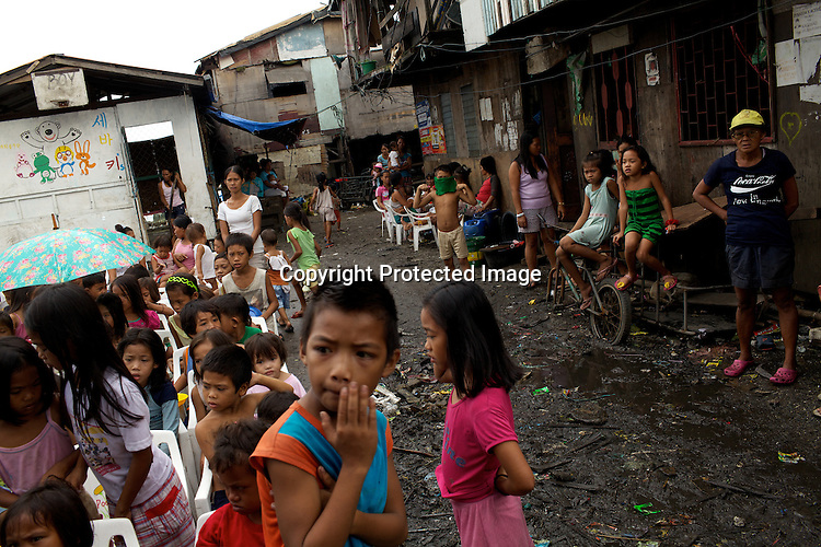 Children gather as volunteers from the Project Pearl distribute (not in picture) food in the slums of Smokey Mountain-II in Manila in Philippines. Photo: Sanjit Das