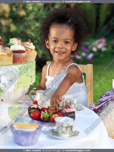 Happy smiling three year old girl having a party outdoors