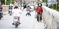 Old Vietnamese Lady Returning from Hoi An Market, Vietnam. The crowded streets and stalls of Hoi An market are are full to bursting point with locals buying and selling fruit, vegetables, fresh fish and hand-made crafts. Hoi An is a small town in Central Vietnam, which has been named a UNESCO World Heritage Site due to its history as a working port town. It is one of the most visited tourist destinations in Vietnam thanks to the characterful, narrow streets, lively market and abundance of bars, restaurants and shops, most of which now cater for the tourist market.