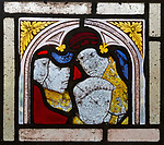 Close-up of medieval style stained glass showing faces of people, Ufford church, Suffolk, England, UK