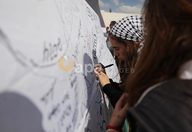 "A girl writes on a Palestinian flag during an attempt to break the Guinness World Record for the ""largest Palestinian flag"", in the West Bank city of Ramallah October 28, 2014. Photo by Shadi Hatem"