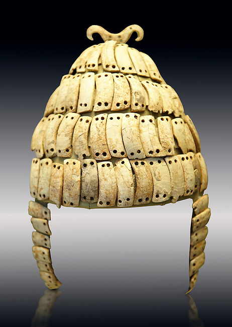 """Boar's tusk helmet with cheek guards and double bone hook on top. Tomb 515 Mycenae, Greece. 14th-15th century BC. National Archaeological Museum, Athens.. The Boar's tusk helmet was described in the Iliad as follows """"Meriones gave Odysseus a bow, a quiver and a sword, and put a cleverly made leather helmet on his head. On the inside there was a strong lining on interwoven straps, onto which a felt cap had been sewn in. The outside was cleverly adorned all around with rows of white tusks from a shiny-toothed boar, the tusks running in alternate directions in each row..?Homer, Iliad 10.260-5"""""""