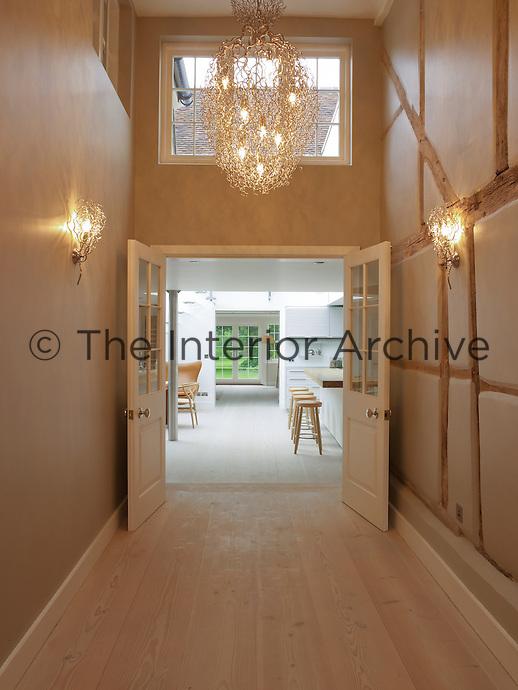 Double doors open into the kitchen dining area from the illuminated corridor