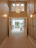 Double doors open into the kitchen dining area from the illuminated corridor