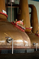 Resembling alchemists' alembics three huge antique copper stills in one of the distilleries on the island of Islay