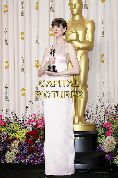 Anne Hathaway (wearing Prada).85th Annual Academy Awards held at the Dolby Theatre at Hollywood & Highland Center, Hollywood, California, USA..February 24th, 2013.pressroom oscars full length pink sleeveless silk satin dress award trophy winner .CAP/ADM.©AdMedia/Capital Pictures.